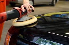 Bil som specificerar, polerad svart bil vid poleringsmaskinen arkivbilder