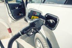 Bil som tankar på bensinstation Att att fylla maskinen med bränsle Arkivbild