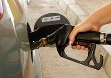 Bil som tankar på bensinstationen Arkivfoto
