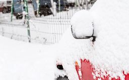 Bil som täckas med snö efter en storm Arkivfoto