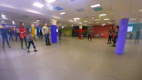 Many people of children and adults go roller-skating on the rollerdrom