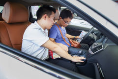 Bilaffärsbiträde som talar med den presumtiva kinesiska märkesbilköparen på den Dongguan bilutställningen Royaltyfria Bilder