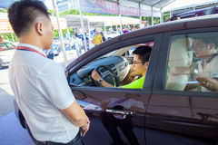 Bilaffärsbiträde som talar med den presumtiva kinesiska märkesbilköparen på den Dongguan bilutställningen Arkivfoto
