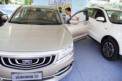 Bilaffärsbiträde som talar med köparen för bil för presumtivt Geely märke den kinesiska på den Dongguan bilutställningen Royaltyfri Foto