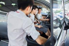 Bilaffärsbiträde som talar med presumtiva kinesiska märkesbilköpare på den Dongguan bilutställningen Royaltyfri Fotografi