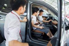 Bilaffärsbiträde som talar med presumtiva kinesiska märkesbilköpare på den Dongguan bilutställningen Royaltyfria Foton
