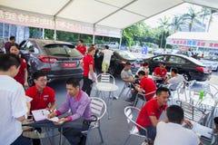 Bilaffärsbiträden som talar med presumtiva kinesiska märkesbilköpare på den Dongguan bilutställningen Royaltyfria Bilder