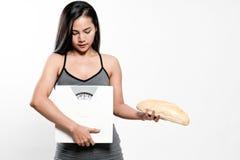 Bilance e pane della tenuta della donna di dieta Immagini Stock Libere da Diritti