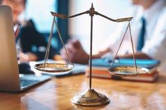 Bilancia della giustizia sul fondo di legno della tavola con la donna di affari e gli avvocati maschii che discutono i documenti  fotografia stock