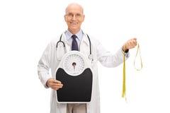 Bilancia della tenuta di medico e nastro di misurazione Fotografia Stock Libera da Diritti