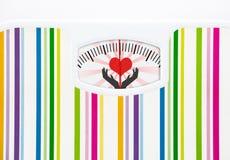 Bilancia pesa-persone con cuore sul quadrante Fotografie Stock