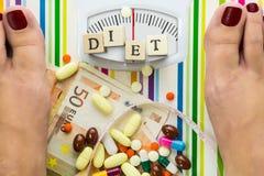 Bilancia pesa-persone con le pillole ed i soldi Fotografia Stock