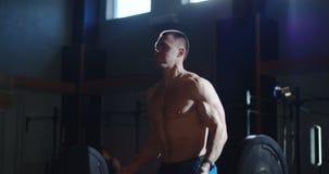 Bilanciere di sollevamento del forte atleta senza camicia in palestra soleggiata video d archivio