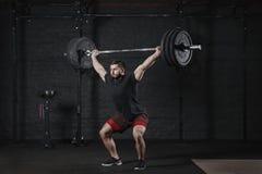 Bilanciere di sollevamento del giovane atleta del crossfit al di sopra alla palestra Uomo che pratica gli esercizi powerlifting d immagine stock