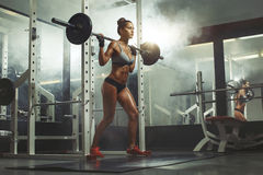 Bilanciere di sollevamento della donna con peso in palestra Immagine Stock