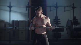 Bilanciere di sollevamento tatuato dello sportivo in palestra video d archivio