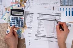 Bilancio domestico annuale del calcolatore e pensare al suo costo Fotografia Stock