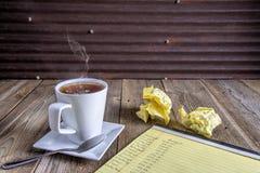Bilancio sulla carta del blocco note, tazza di caffè di cottura a vapore caldo fotografie stock