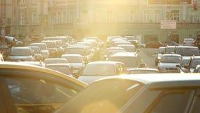 Bilar för solljus för stadstrafikstockningskymning klibbade gatan, ljus rörelse lager videofilmer
