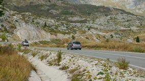 Bilar går på vägen i bergen med fält i Durmitor parkerar stock video