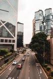 Bilar i Hong Kong som kör på en huvudvägnexto till Lippo de tvilling- byggnaderna royaltyfri bild