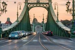 Bilar i linje på Liberty Bridge i den Budapest Ungern på solnedgången Royaltyfri Fotografi