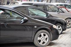 Bilar i parkeringsplatsen. Arkivfoton