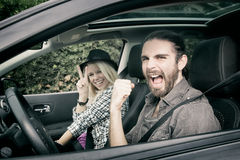 Bilar - kalla hipsterpar som kör i nytt skrika för bil som är lyckligt och att se kameran Royaltyfria Foton