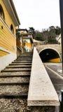 Bilar måste gå till tunnelen, och folket klättrar upp trappan på royaltyfria bilder