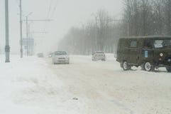 Bilar oa en väg i snöstormarna Royaltyfri Fotografi