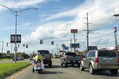 Bilar och en cykel stoppade på en trafikljus i staden av Sulphur i Louisiana Royaltyfria Foton