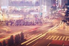 Bilar och folk som korsar en upptagen Tokyo genomskärning Arkivbild