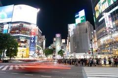 Bilar och gångare som går på gataplats av trafik på den Shibuya korsningen i Tokyo royaltyfri bild
