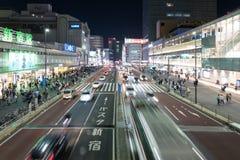 Bilar och gångare som går på gataplats av trafik på den Shinjuku stationskorsningen i Tokyo arkivfoton