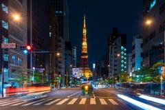 Bilar och g?ngare som g?r p? gataplats av trafik p? den Tokyo tornkorsningen i Tokyo royaltyfri fotografi