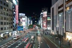 Bilar och g?ngare som g?r p? gataplats av trafik p? den Shinjuku stationskorsningen i Tokyo royaltyfri foto