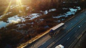 Bilar och halva lastbilar för frakter som laddas med gods som kör längs en tom huvudväg som transporterar last på morgongryning stock video