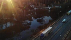 Bilar och halva lastbilar för frakter som laddas med gods som kör längs en tom huvudväg som transporterar last på morgongryning lager videofilmer