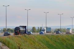 Bilar och lastbilar flyttar sig på den moderna huvudvägen med lyktor Royaltyfri Fotografi