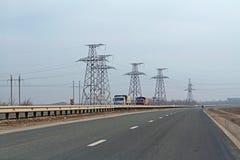 Bilar och lastbilar som kör på huvudvägen i bakgrunden av överföringslinjer i den Volgograd regionen Arkivfoto