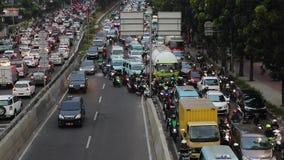Bilar och motorcykel på trafikstockning i Jakarta arkivfilmer