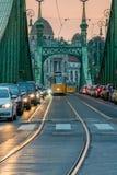 Bilar och spårvagnar på solnedgången på Liberty Bridge i den Budapest Ungern Arkivfoto