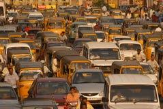 Bilar och två person som drar en skottkärra som väntar i en trafik Fotografering för Bildbyråer
