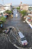 Bilar och uppsamlingar kör till och med vattnet i en översvämmad gata av Bangkok på 04. November 2011 Royaltyfri Foto