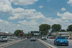 Bilar på en huvudsaklig gata i staden Rundu i norden av Namibia Arkivfoto