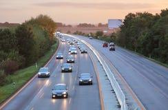 Bilar på huvudvägvägen på solnedgången arkivfoto
