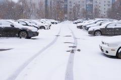 Bilar på parkeringen nära det bostads- huset som täckas av snö arkivfoto