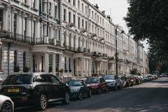 Bilar parkerade tillsammans med terrasserade hus i Notting Hill, London, U arkivfoto