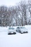 Bilar parkerar med snöberget Royaltyfri Foto