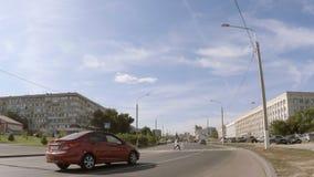 Bilar passerar en gångare på en stadsväg stock video